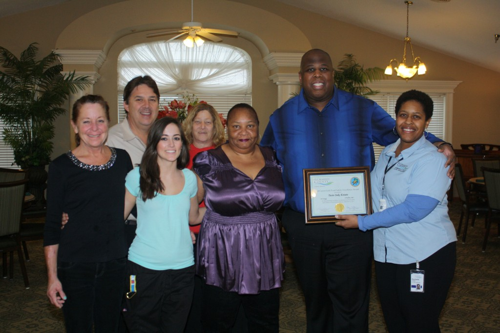 (from left) Twin Oaks Estate dietary staff members Tina Ziegler, Twin Oaks CEO Tim Blattel, Courtney Markos, Roni Stringer, Bruetta Ward, and Dietary Manager Larry Conner receive the 24 Carrot Gold Food Safety Excelelce Award from St. Charles County Health Inspector Rochelle Howell.